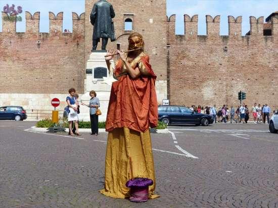 Artista di strada musicista sui trampoli in via Roma (sullo sfondo Castelvecchio) a Verona