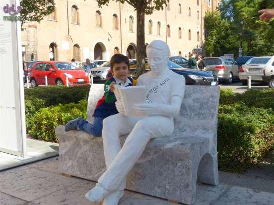 Bambino con istallazione La lettura di Enrico Pasquale per Marmomacc and the City Piazzetta Navona Verona