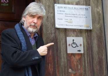 Don Marco Campedelli indica il logo disabili per l'entrata accessbile alla Chiesa di San Nicolò all'Arena