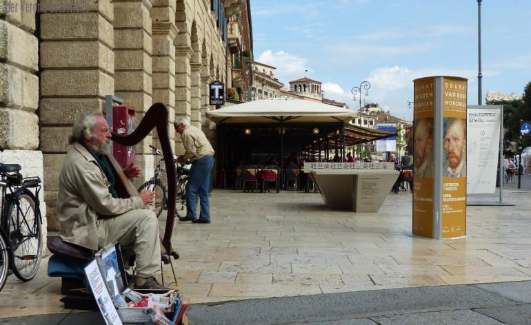 Installazione Ping Pong Pang, design Giorgio Canale, tra tavolo da ping pong e rimando a La Traviata, in Piazza Bra per Marmomacc & the City 2015, e suonatore d'arpa, Verona