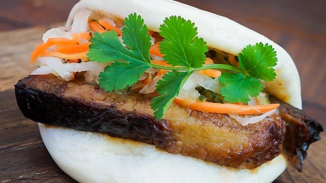 Black garlic soy-braised pork belly bao with pickled vegetables