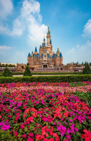 enchanted-storybook-castle-daytime-puffy-clouds-flowers-shanghai-disneyland