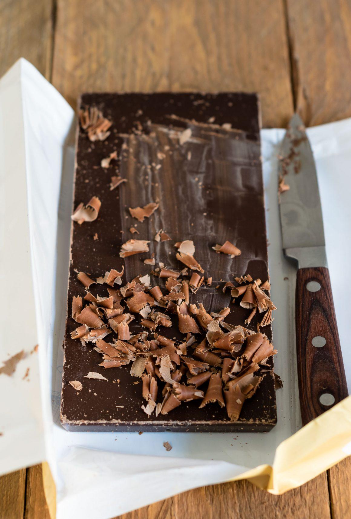 riccioli di cioccolato su una tavoletta fondente e un coltello in parte