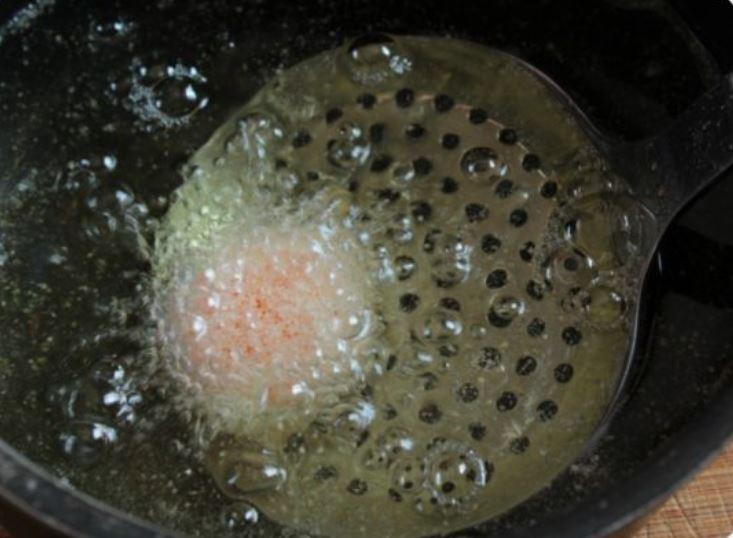 schiumarola che immerge il tuorlo nell'olio bollente
