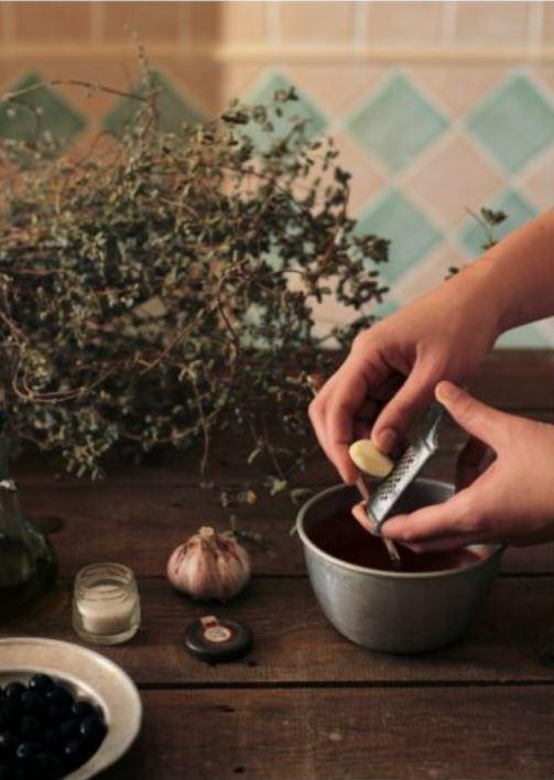 mano che grattugia l'aglio in una ciotola
