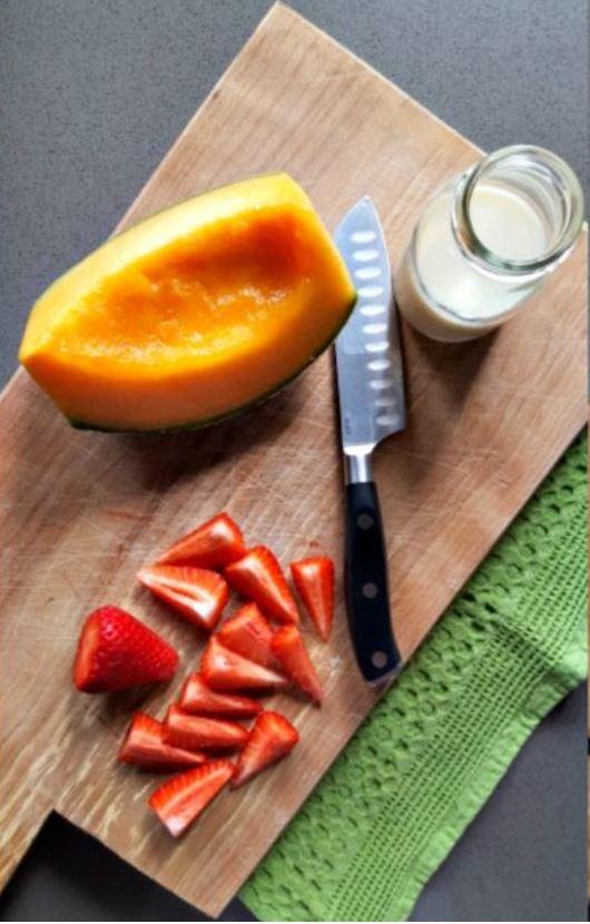 tagliere con una fetta di melone e fragole a spicchi