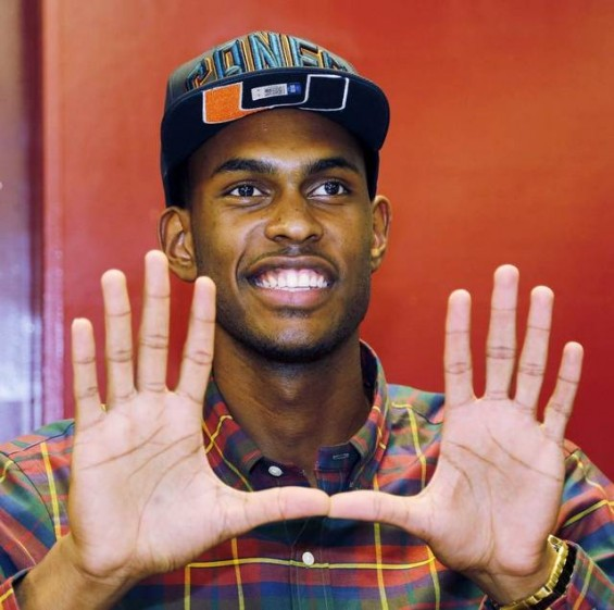 "Miami recruit Dewan Huell flshes the ""U"" to signify his intent to join the Hurricanes / Miami Herald"