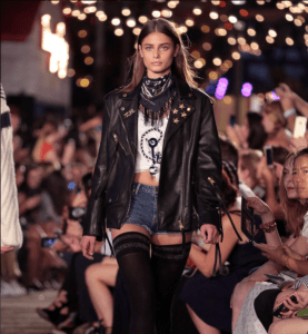Taylor Hill wore the same top and scarf as Hadid. However, the addition of the addition of the oversize leather jacket and knee high socks makes the outfit more trendy.