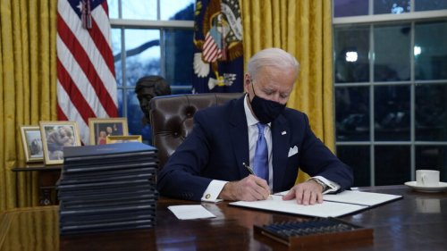 President Joe Biden signs his first executive orders in the Oval Office