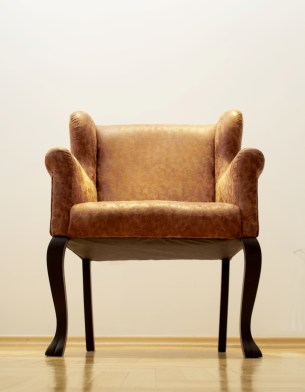 Beautiful, brown leather armchair shot from the floor with bright lighting.