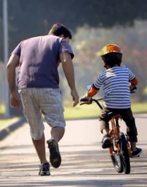 Pai ensinando o filho a andar de bicicleta