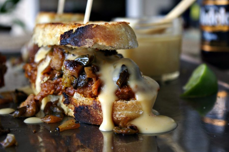 Chipotle Lime Brisket Sandwich topped with Sauteed Brussels Sprouts, Onions and Peppers AND Modelo Cheese Sauce