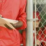 coach with scorebook representing questions to ask college coaches