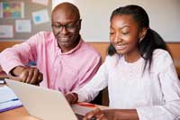 Father helping daughter with test prep decisions at laptop