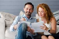 couple sitting on sofa reading about the 7 ways to compare colleges