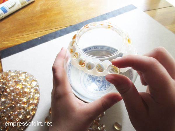 She Starts By Adding Flat Marbles To A Plastic Container