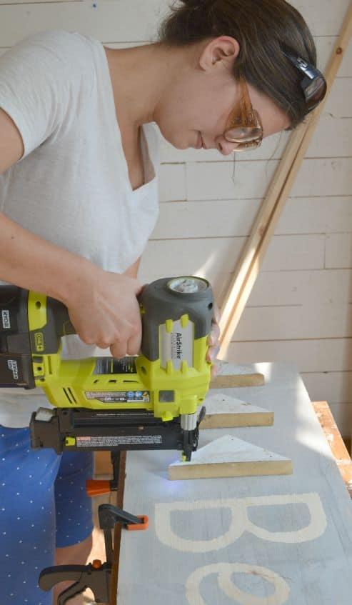 DIY Scrap Wood Sign Brad Nailing the Embellishments