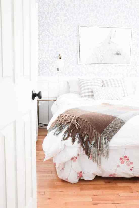Bright coastal bedroom with aged bronze door hardware