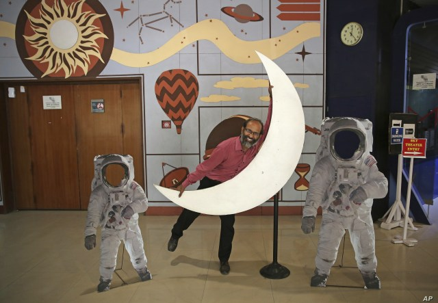 An employee playfully hugs a cutout of a crescent moon at the Nehru Planetarium in New Delhi, India, July 11, 2019. India is preparing its second unmanned mission to the moon, this one aimed at landing a rover near the unexplored south pole.