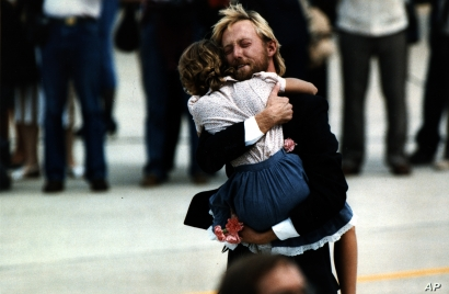 FILE - While holding carnations he carried off the plane, former hostage Victor Amburgy hugs an unidentified girl after his arrival at Andrews Air Force Base, July 2, 1985. Thirty former hostages from TWA flight 847 were greeted on American soil by President and Mrs. Reagan.