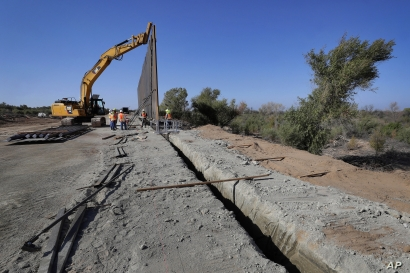 Government contractors erect a section of Pentagon-funded border wall along the Colorado River, Tuesday, Sept. 10, 2019 in Yuma, Ariz. The 30-foot high wall replaces a five-mile section of Normandy barrier and post-n-beam fencing, shown at left,…