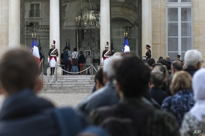 People line up to sign a condolence book for late French President Jacques Chirac, Friday Sept. 27, 2019 in the courtyard of the Elysee Palace in Paris. Mourners are signing memory books, flags are lowered and French politicians from across the…