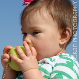 Baby biting an apple