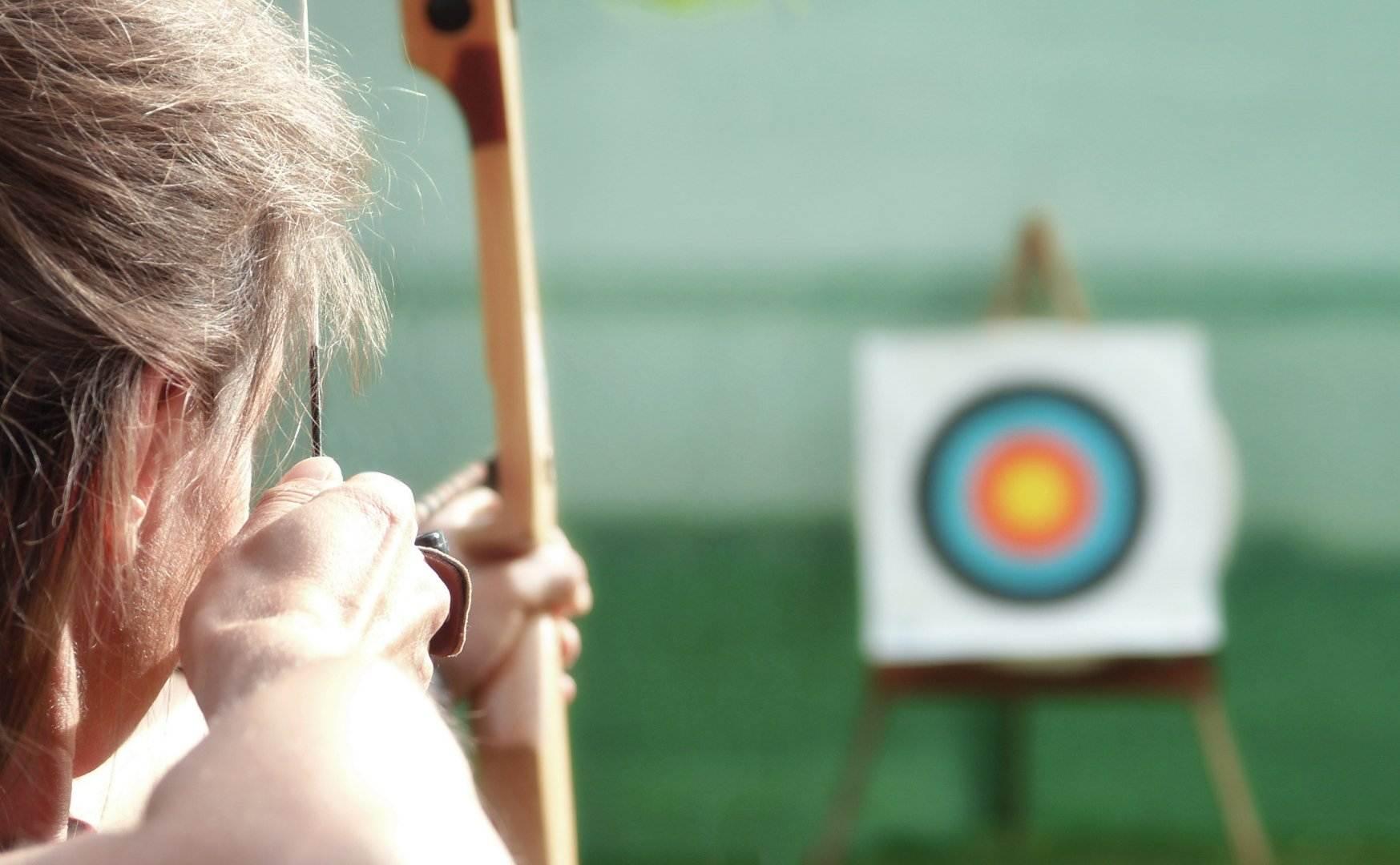 Mujer apuntando a una diana con un arco.