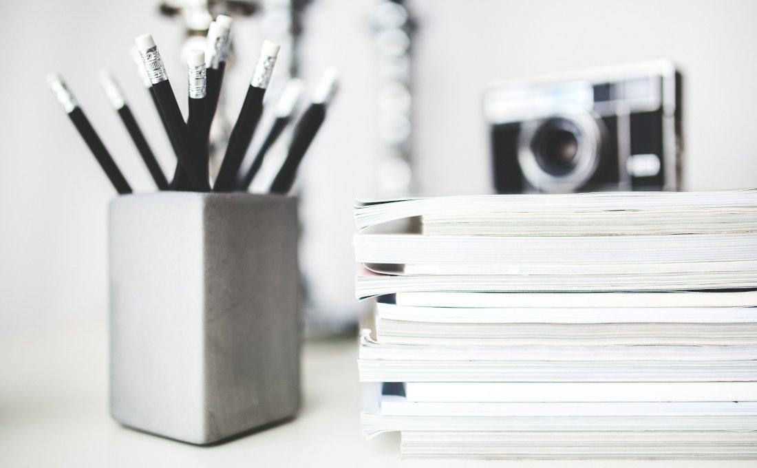 Imagen con unos lápices, unas revistas y una cámara