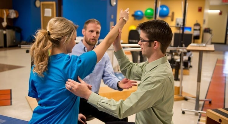 Shane McClinton, center, instructs a student working with a patient to improve shoulder function.