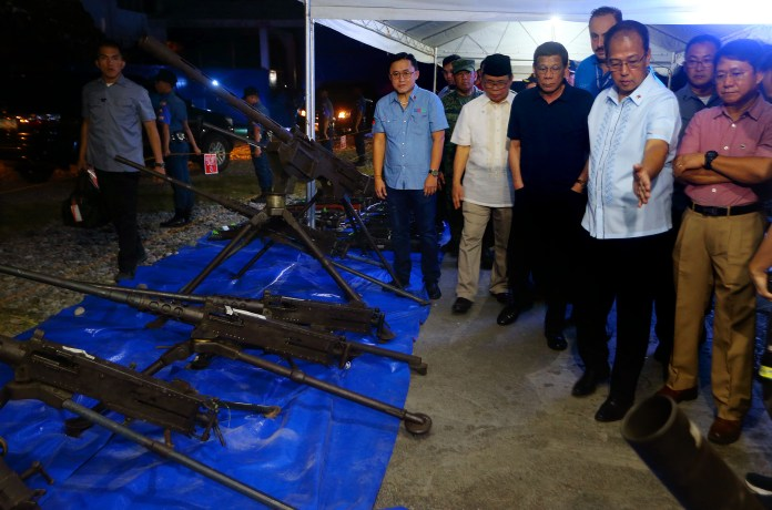 MILF Chairman Al Haj Murad Ebrahim and Presidential Peace Adviser Carlito G. Galvez Jr. (right) showcased to President Rodrigro Duterte (center) on Saturday September 7, 2019, the 920 high-powered firearms including 60mm and 81mm mortars; 7 crew-mounted M2 Browning caliber 50 machineguns; and 500 RPG rocket launchers which were voluntarily turned over 1,060 former MILF combatants to the International Decommissioning Body (IDB). As promised the government handed 100,000 cash to each decommissioned former MILF combatant intended for the scholarships and other socio-economic benefits for their family and community held at Gymnasium old Provincial Capitol compound, Bgy Simuay Sultan Kudarat, Maguindanao.>Mark Navales