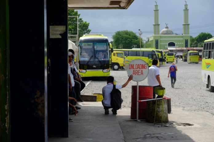 A mosque stands in the background in this photo of buses at the Ceres southern bus terminal in Bacolod City. Since the 1960s when it first began operating, Ceres has expanded its operations to Luzon and   Mindanao. Like the deeply divided South, its family members have split into two camps, however, affecting its business operations. | Photo by Jose Aaron C. Abinosa
