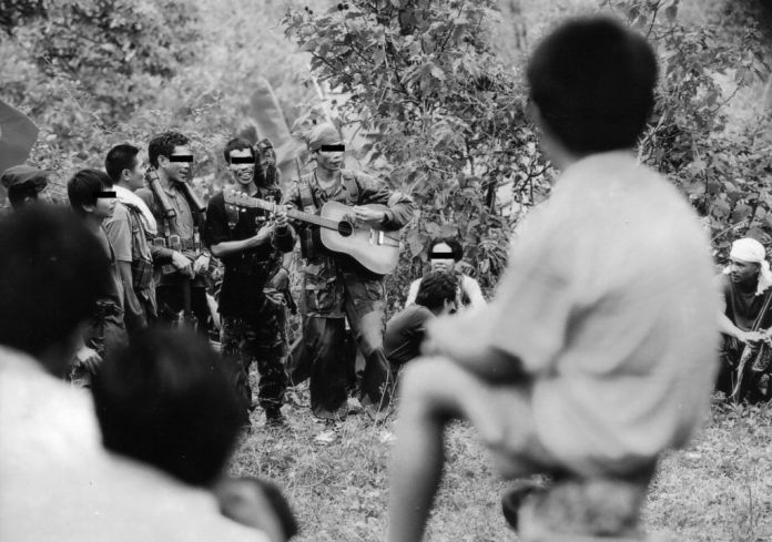 SINGING WARRIORS | Red fighters of the New People's Army play a guitar and sing revolutionary songs during a celebration of the Communist Party's founding anniversary in Negros island, Philippines | The CPP is the political wing of the NPA | This was originally shot using colored film | Photo by Julius D. Mariveles