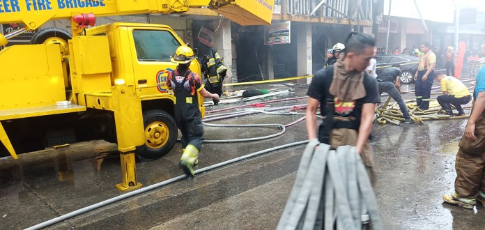 DRENCHED. Volunteer firefighters unravel fire hoses for longer reach to help fight fire better.