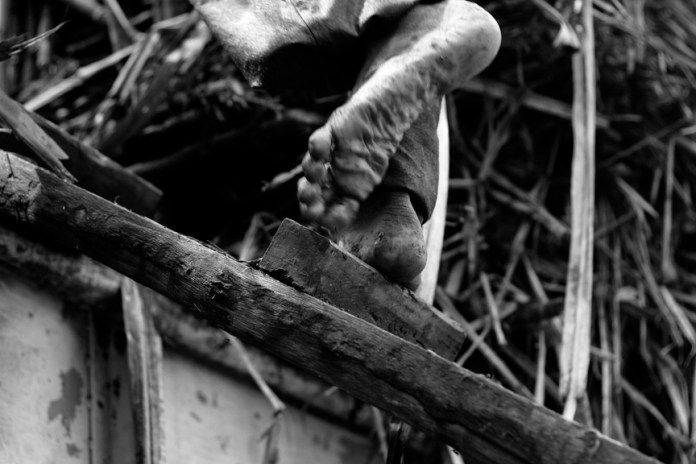 The calloused foot of a sugarworker loading cut canes on a truck is shown in this photo taken during the opening of the milling season in 2012. | DNX file photo and text by Julius D. Mariveles