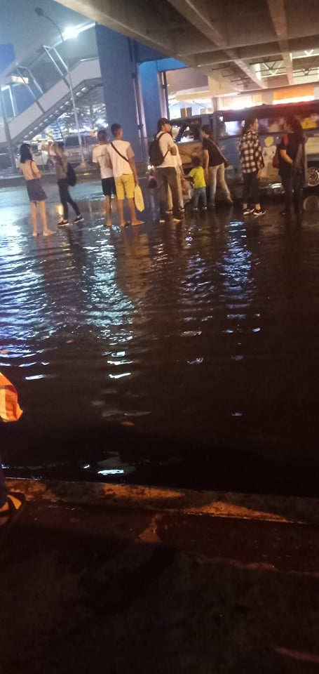 People are left stranded under SM City Bacolod – East bridge due to heavy rains. | Photo by Richard Meriveles