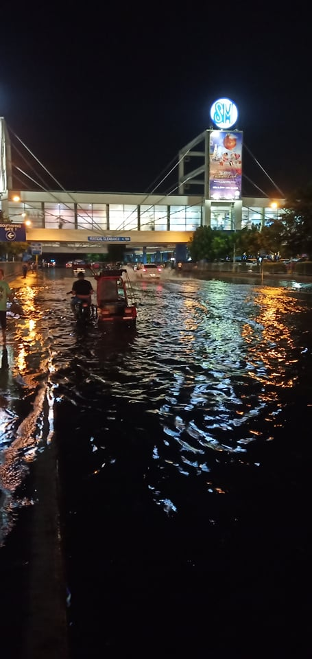 A tricycle crosses the gutter-high water along SM City Bacolod after a strong rainfall that lasted to almost half an hour. | Photo by Richard D. Meriveles