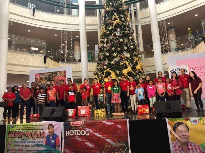 Under the tree. Rotary Club officers and members pose with some of the beneficiaries of the Wish Upon a Star project of the civic organization in partnership with Robinsons Mall.