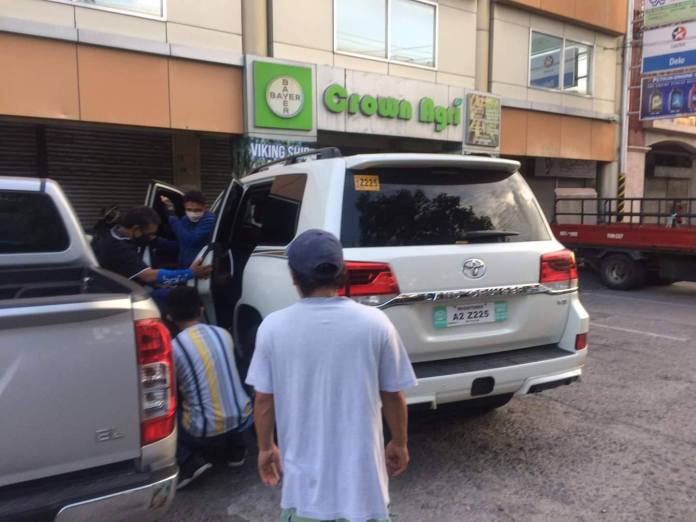 Bystanders and kibitzers look at the slumped figure of the businessman later identified as Roland Tan, owner of an agri supplies shop. | Photo by Banjo Hinolan