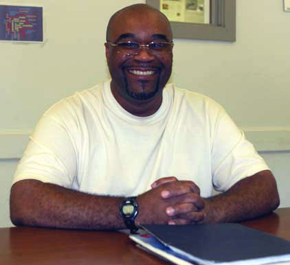 Portrait of inmate John Fitzpatrick smiling while sitting at a classroom desk inside Cedar Creek Corrections Center