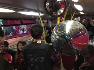 A group of people on a bus with a disco ball in the front of the view