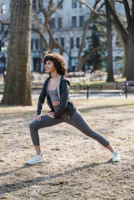 fit black woman stretching legs in park in daylight