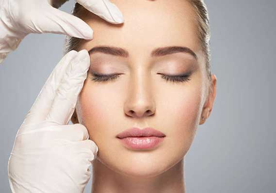 doctors hands examining female patients face for aesthetics treatment