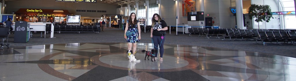 Veronica with Hestia and Scarlet with Gigi standing in an uncrowded part of the terminal