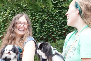 Veronica and Lizzy laugh together while their Japanese Chin, Hestia and Kitten, look on.