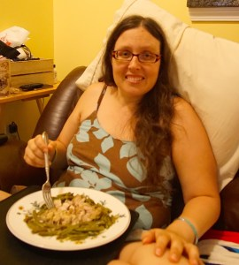 Veronica smiling with a plate of cut up chicken and green beans