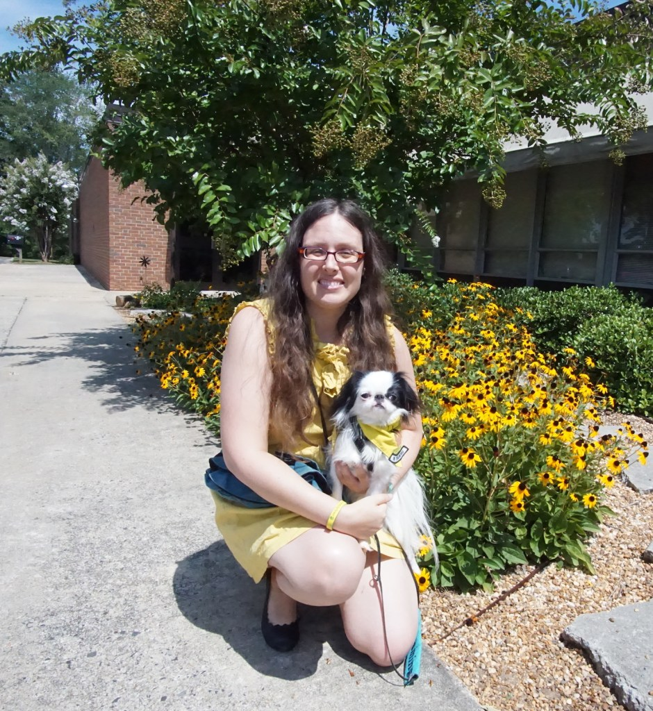 Veronica in a yellow dress, holding Hestia in a yellow and black harness and yellow bandana, sitting in front of some yellow flowers