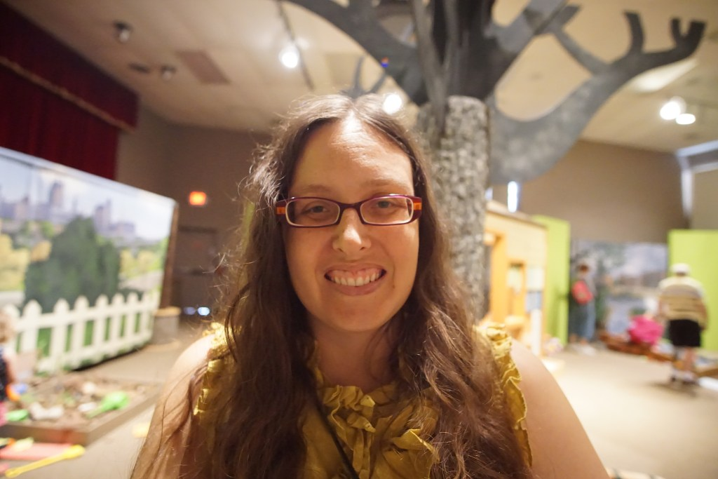 Closeup of Veronica's face with long curly brown hair and purple and orange glasses