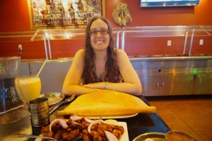Veronica sitting happily in front of a large dosa