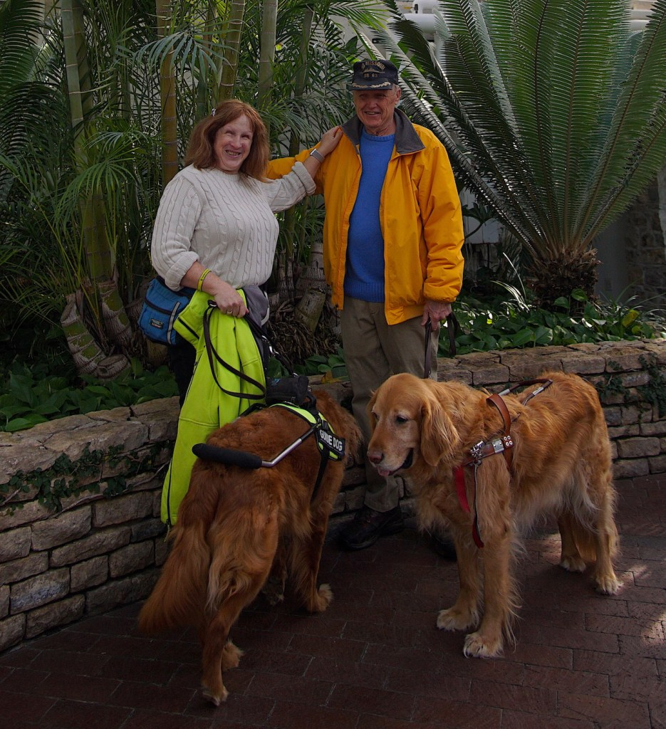 Jenine and Roger, Kent and Linus standing in front of some palm trees.